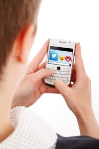 woman posting to social media from mobile phone